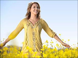 Vrouw staat in veld bloemen en ervaart Gods liefde