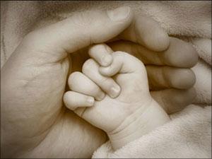 hand van kind geborgen in Gods handen van liefde
